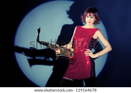 Professional musician posing with her saxophone at studio.