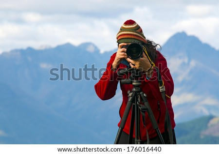 Professional nature and landscape photographer (woman) at work outdoor on location. - stock photo