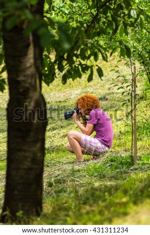 Professional nature photographer lady with her camera in the field