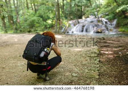 Professional nature photographer lady with her camera shooting a waterfall