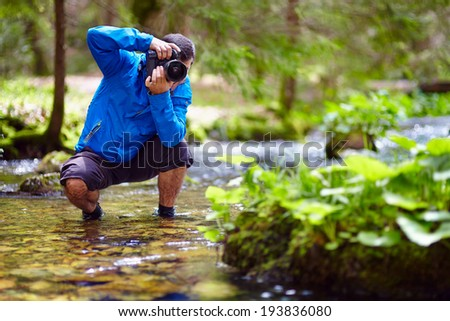 Professional nature photographer taking photos by the river side - stock photo