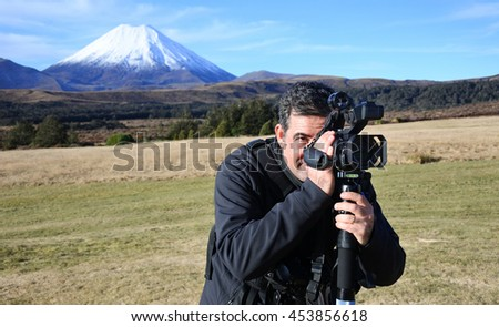 Professional nature, wildlife and travel videographer filming Mount Ngauruhoe outdoors during on location photo assignment in in Tongariro National Park New Zealand. copy space. - stock photo