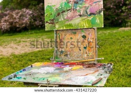 Professional old artist's sketchbook  with different artist's equipment colorful palette paletteknife paints and paintbrushes outdoors - stock photo