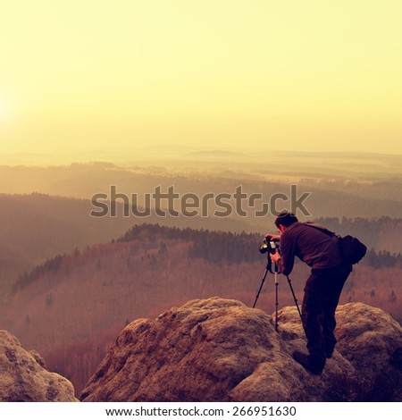 Professional on location and nature photographer  takes photos with mirror camera on peak of rock. Dreamy fogy landscape, spring orange pink misty sunrise in a beautiful valley below.