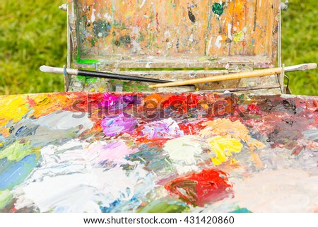Professional painter's sketchbook  with multicolored palette of blended oil paints with paintbrushes outdoors - stock photo