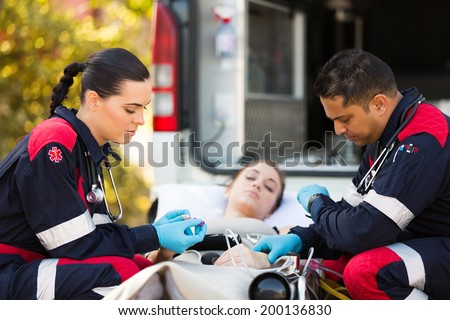 professional paramedics giving unconscious young woman first aid