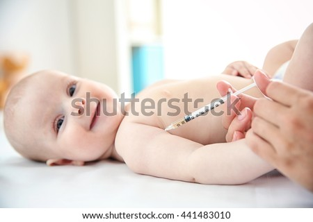 Professional pediatrician vaccinating baby, close up - stock photo