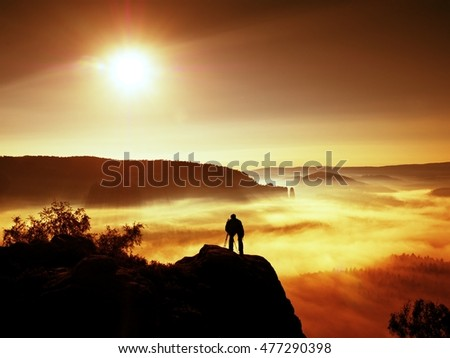 Professional photographer on location takes photos with mirror camera on peak of rock. Dreamy fogy landscape, spring orange pink misty sunrise in a beautiful valley below.