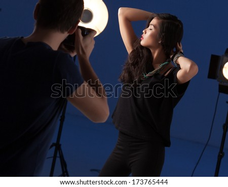 Professional photographer photographing a fashion model at a studio. - stock photo