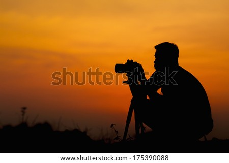 Professional Photographer silhouette at sunset, in Thailand. - stock photo