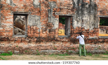 Professional photographer take a picture of Reclining Buddha Statue through Window at Wat Phut thaisawan in Ayutthaya , Thailand - stock photo