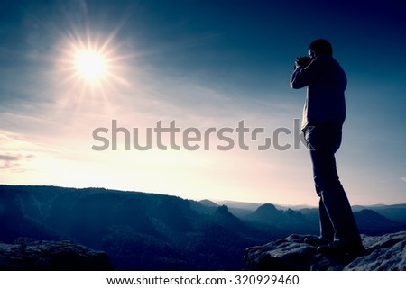 Professional photographer takes photos with big camera on peak of rock. Dreamy misty landscape, hot Sun above - stock photo
