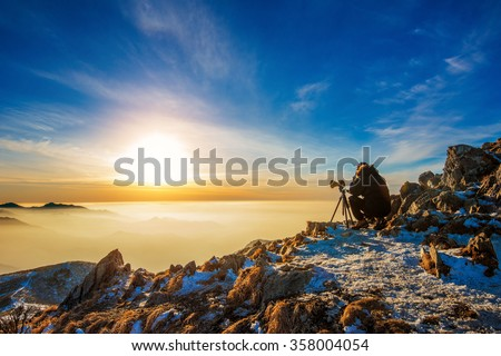 Professional photographer takes photos with camera on tripod on rocky peak at sunset. - stock photo