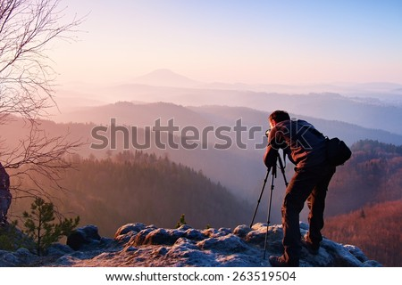 Professional photographer takes photos with camera on tripod on rocky peak. Dreamy fogy landscape, spring orange pink misty sunrise in a beautiful valley below - stock photo