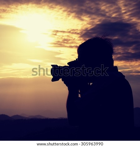 Professional photographer takes photos with mirror camera on peak of rock. Dreamy landscape, orange  Sun at horizon