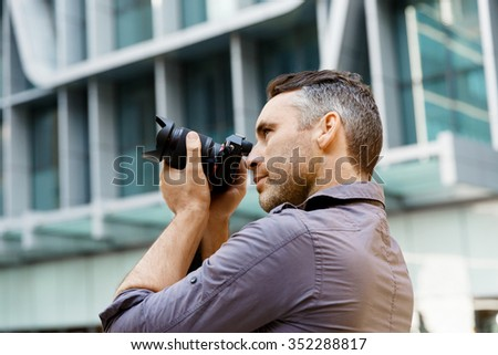 Professional photographer taking picture in city