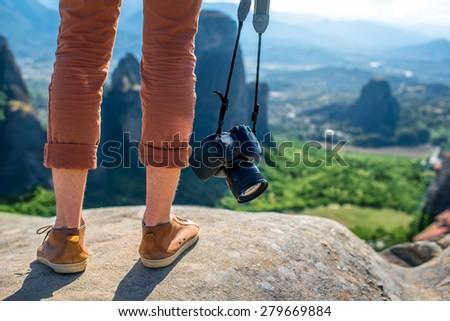 Professional photographer with photo camera standing on the top of mountain on beautiful scenic clif background near Meteora monasteries in Greece. Close up back view on legs and camera. - stock photo