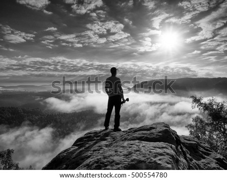 Professional photographer with tripod and camera thinking. Creamy heavy fog in gulch. Dreamy fogy  mountains. Misty sunrise in a beautiful valley below