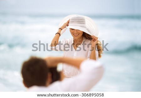 Professional photographer working with a model on the beach - stock photo