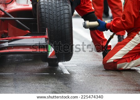 Professional racing team at work during a pitstop of a race car in the pitslane during a car race. - stock photo