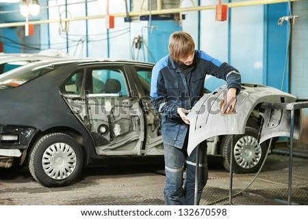 professional repairman worker in automotive industry sanding plastic body car bumper - stock photo