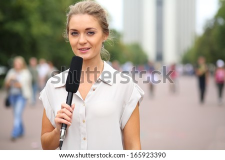Professional reporter beautiful girl standing on the street with a microphone in hand - stock photo