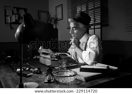 Professional reporter working late at night at his desk with vintage typewriter, 1950s style.
