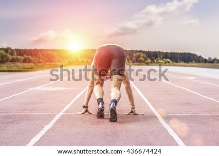 Professional runner taking ready to start position against bright sunlight