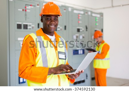 professional senior afro american control room technician using laptop - stock photo