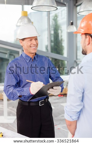 Professional senior architect is talking with the foreman about new building. He is holding a folder of document and drawing sketch. The men are standing and smiling - stock photo