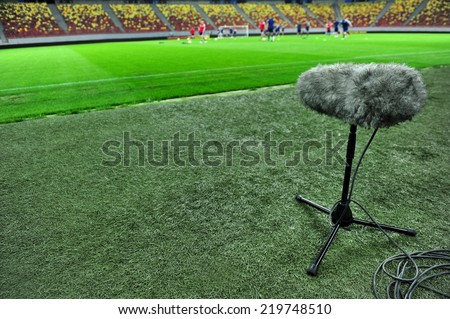 Professional sport microphone on a football field with players training in the background - stock photo