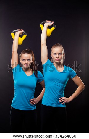 Professional sporty women working out with kettlebells, isolated on gray background. - stock photo