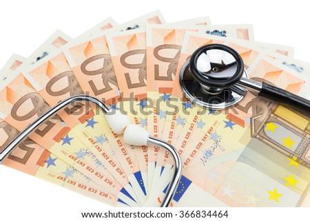 Professional stethoscope lying on pile of euro notes isolated on white background - stock photo