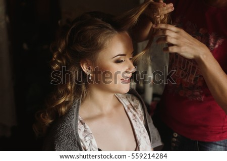 Professional stylist doing hairstyle for beautiful woman, blonde bride getting her hair done by hairdresser, morning wedding preparation closeup