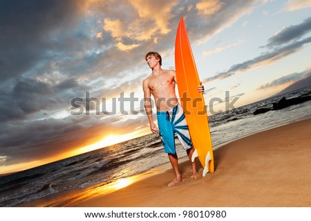 professional surfer holding a surf board - stock photo