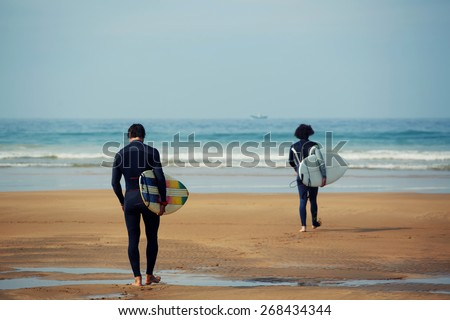 Professional surfers in black diving suits ready to surf walk to the ocean, two surfers carrying their surfboards going to the sea - stock photo