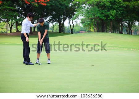 Professional teaching teenager boy to play golf - stock photo