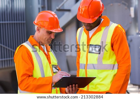 professional technical workers working at power plant - stock photo