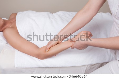 Professional  therapist doing  remedial deep tissue massage on muscles of a woman's  forearm
