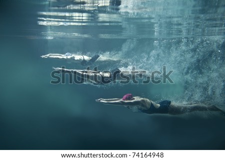 Professional three swimmers under water isolated - stock photo