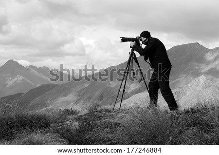 Professional travel on location and nature videographer/photographer (man) photographing and video nature and landscape outdoor.(BW) - stock photo