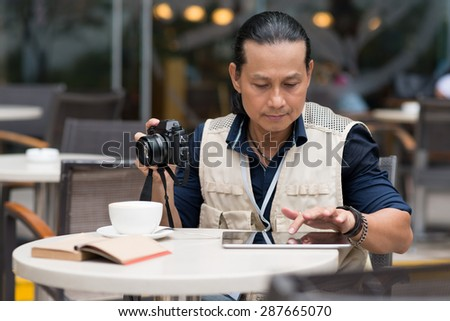 Professional Vietnamese photographer using tablet computer in the cafe