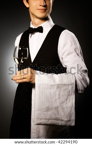 professional waiter in uniform is serving wine - stock photo