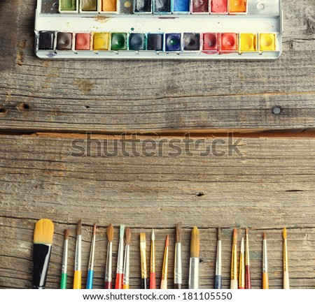 Professional watercolor aquarell paints in box with brushes on old wooden board - stock photo