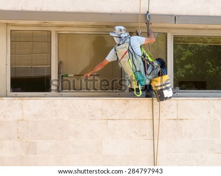 Professional window washer cleaning windows on a building.