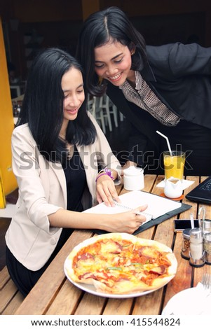 Professional woman assisting her friend that doing some works in a restaurant - stock photo