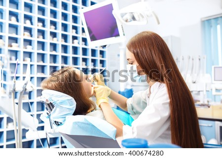 Professional woman dentist doctor working .  woman at dental clinic. lady woman at dentist taking care of teeth.Dental care for people. Dentist holding dental device for fixing teeth. - stock photo