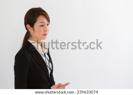 Professional woman in a business suit against white wall listening to someone with a cell phone in her hands - stock photo