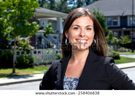 Professional woman outside in a neighborhood looking into the camera. - stock photo