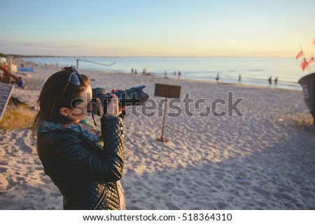 professional woman photographer on the beach, summer time